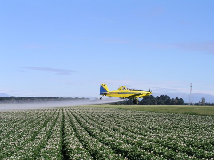 Plane spraying potato field